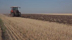 O trator move-se através do campo, arando a terra após a agricultura da colheita vídeos de arquivo