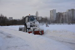 O trator nevado de um serviço do municipal joga a neve das passagens no parque da cidade na manhã do inverno Fotos de Stock