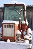 O trator nevado vermelho velho Fotografia de Stock Royalty Free