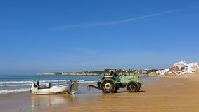 O trator puxa um barco de pesca fora da água na maré baixa Na praia arenosa longa, larga, fina do pescador de Armacao de Pera, Si Fotos de Stock