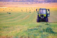 O trator recolhe a grama seca na palha imagem de stock