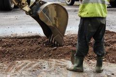 O trator remove a parte do solo com uma cubeta antes de asfaltar a estrada para remendar O contramestre do lado dos suportes dos  fotos de stock royalty free