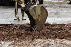 O trator remove a parte do solo com uma cubeta antes de asfaltar a estrada para remendar O contramestre do lado dos suportes dos  foto de stock