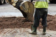 O trator remove a parte do solo com uma cubeta antes de asfaltar a estrada para remendar O contramestre do lado dos suportes dos  imagens de stock