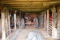 O trator velho estacionou em um celeiro de madeira rústico imagem de stock royalty free