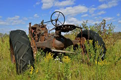 O trator velho estacionou nas ervas daninhas amarelas coloridas do outono Fotografia de Stock Royalty Free