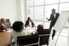O treinador africano do negócio dá a apresentação para a equipe na reunião da placa fotografia de stock