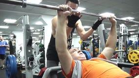 O treinador ajuda o homem gordo a colocar um pescoço vazio de uma barra, vídeo do divertimento filme
