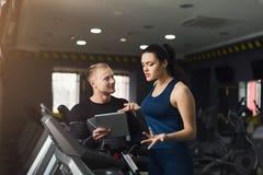 O treinador da aptidão ajuda a mulher no instrutor elíptico imagens de stock