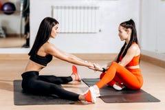 O treinador da aptidão tem um exercício de esticão individual com a menina magro nova na sala da aptidão ao lado do espelho foto de stock