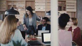 O treinador do negócio da mulher dá sentidos à equipe O chefe fêmea europeu seguro novo conduz o escritório multi-étnico que enco vídeos de arquivo