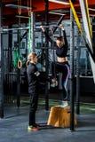 O treinador ensina para levantar em uma menina horizontal do barl Fotografia de Stock
