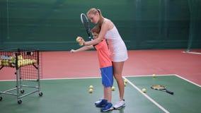 O treinador fêmea vestiu-se no vestido branco curto do esporte está ensinando o rapaz pequeno jogar na corte interna Tênis profis video estoque
