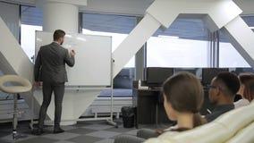 O treinador masculino fala e escreve na conferência em empresa principal dentro vídeos de arquivo