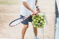 o treinador recolhe o t?nis as bolas na cesta ap?s a forma??o Li??o de t?nis imagem de stock royalty free