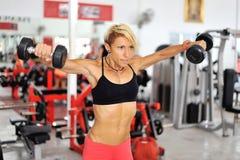 O treinamento atlético da mulher do ajuste empurra no gym fotos de stock