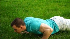 O treinamento caucasiano do homem da aptidão empurra acima o exercício na grama trabalho masculino do atleta exterior vídeos de arquivo