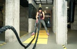O treinamento da menina nova e atrativa bonita que faz a expressão séria da cara quando malhar na batalha ropes no gym fotografia de stock