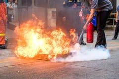 O treinamento de combate ao fogo dos empregados, extingue um fogo foto de stock