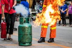O treinamento de combate ao fogo dos empregados, extingue um fogo no cyl do gás foto de stock