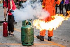 O treinamento de combate ao fogo dos empregados, extingue um fogo no cyl do gás imagem de stock royalty free