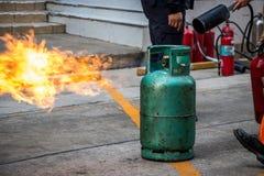 O treinamento de combate ao fogo dos empregados, extingue um fogo no cyl do gás foto de stock royalty free