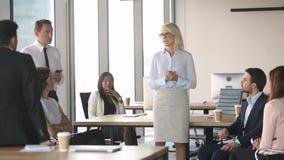 O treinamento velho do mentor do líder da mulher de negócios interna empregados no escritório moderno video estoque