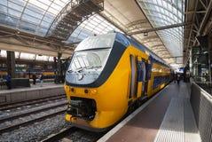 O trem amarelo está na estação de estrada de ferro central em Amsterdão Fotos de Stock Royalty Free