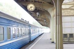 O trem azul está na plataforma no estação de caminhos de ferro com um pulso de disparo imagem de stock