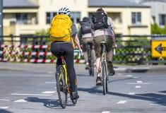O trem de ciclistas amadores cruza o cruzamento pedestre na estrada transversaa nas bicicletas foto de stock royalty free