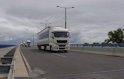 O trem de grandes caminhões conduz em uma estrada com fundo meados de-nebuloso Imagem de Stock Royalty Free