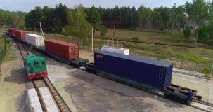 O trem de mercadorias atravessa lentamente a fábrica Estrutura da estrada de ferro na opinião da floresta da parte superior filme