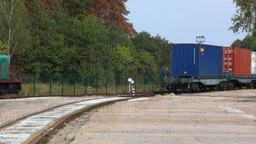 O trem de mercadorias viaja lentamente através da fábrica Recipiente no trem video estoque