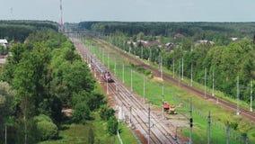 O trem de passageiros da vista superior monta da cidade à vila através do campo filme
