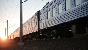 O trem de passageiros passa sobre as trilhas no por do sol video estoque
