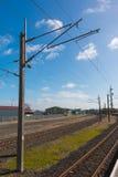 O trem segue o polo da linha elétrica e de poder Foto de Stock