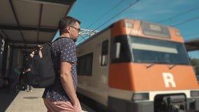 O trem suburbano está chegando em uma estação, pessoa está preparando-se ao embarque video estoque