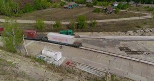 O trem ? um recipiente de primeira classe, uma estrada de ferro na floresta, um trem de mercadorias em um lugar colorido video estoque