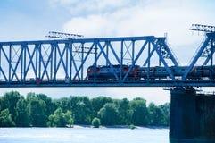 O trem viaja ao longo da ponte de estrada de ferro foto de stock