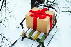 O trenó de madeira velho com um presente na fita vermelha envolvida dourada do presente da caixa de papel, está na floresta do in Imagens de Stock Royalty Free