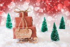 O trenó do Natal no fundo vermelho, meios de Danke agradece-lhe Imagens de Stock Royalty Free