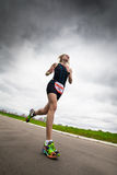 O triathlete da mulher corre durante a competição do triathlon, vista inferior Fotografia de Stock Royalty Free