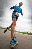 O triathlete dos polegares-acima corre durante a competição do triathlon, vista inferior Imagens de Stock