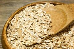 O trigo lasca-se na colher de madeira fotografia de stock royalty free