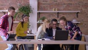 O triunfo louco no trabalho, homem bem sucedido do escritório em vidros aprende boas notícias no portátil e exulta-as com equipe