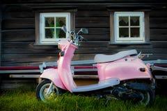 O 'trotinette' cor-de-rosa está estacionado perto da construção de madeira velha Foto de Stock
