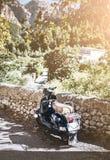 O 'trotinette' de motor estacionou na parede drystone na paisagem mediterrânea imagens de stock royalty free