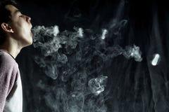 O truque de Vape soa no desempenho do vaper no fundo escuro Fotos de Stock Royalty Free