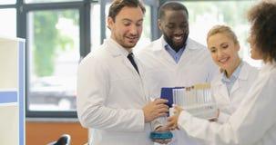 O tubo de ensaio de Team Examine Study Liquid In dos cientistas que trabalham na pesquisa no laboratório, o homem da raça da mist video estoque