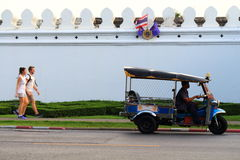 O tuk e o turista de Tuk que andam perto do tuk grande do tuk de Tailândia da parede do palácio são transporte popular Fotografia de Stock Royalty Free